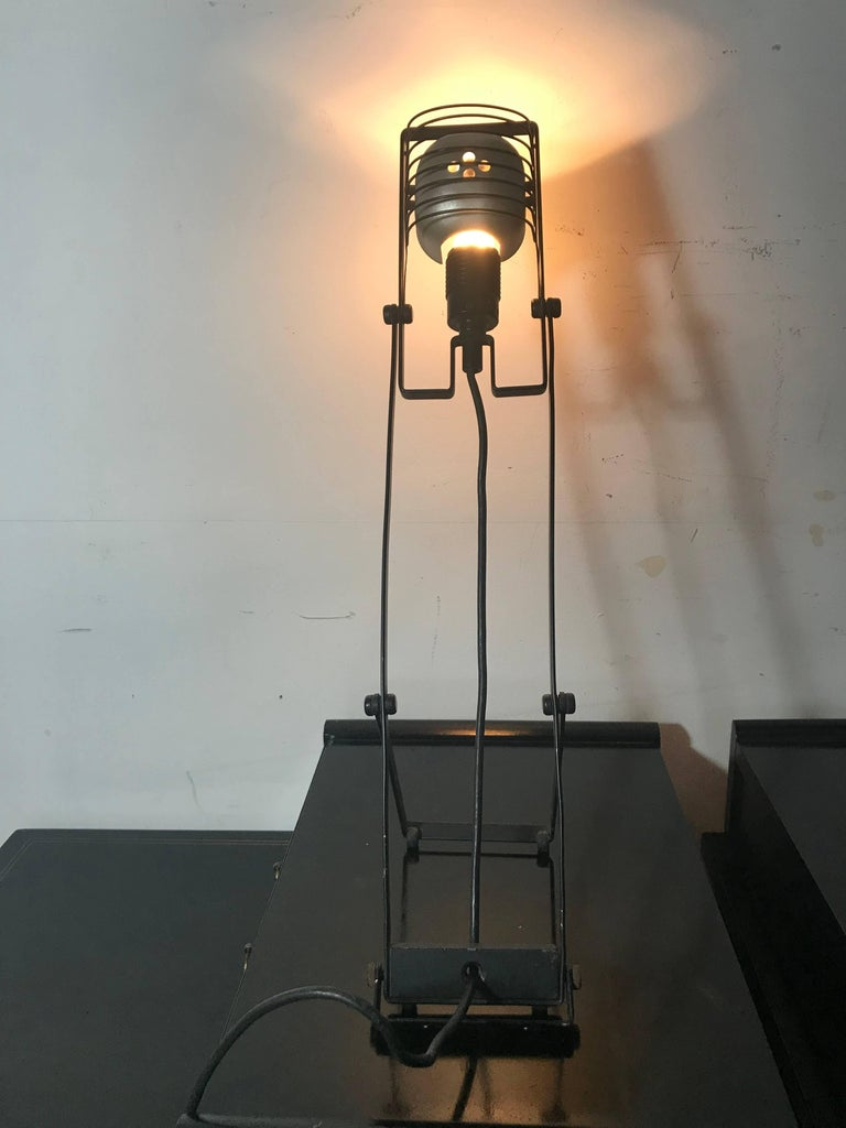 The Sintesi lamp was designed in 1976 by Ernesto Gismondi, the founder of the Italian lighting company Artemide. It is made of aluminium, rubber and plastic.  The Sintesi is part of the permanent collection of the Metropolitan Museum of Art in New