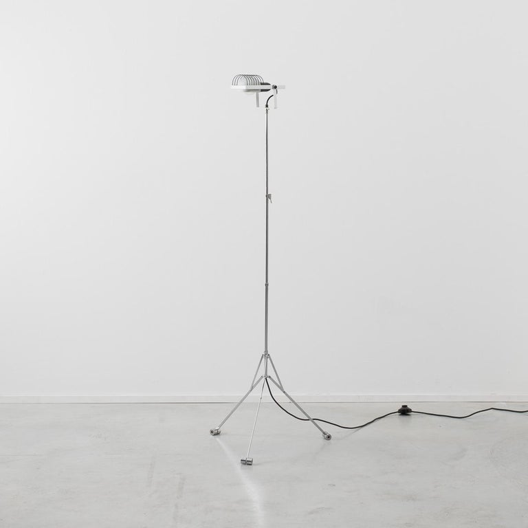 A rare floor standing lamp from the Sintesi range that uses the form of a music Stand turns it into a lamp. In Classic Postmodern style two items that ordinarily would have little in common are designed into each other with tongue firmly in cheek.