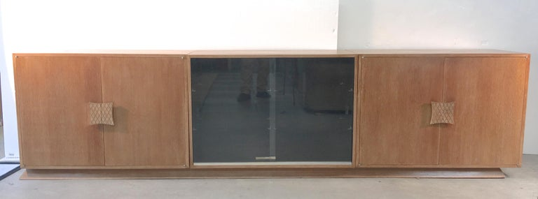 A truly unique three piece storage sideboard consisting of three cerused double door cabinets set on a single trapezoidal plinth base by Viennese architect and designer, Ernst Schwadron. Left and right cabinets consist of double doors mounted with