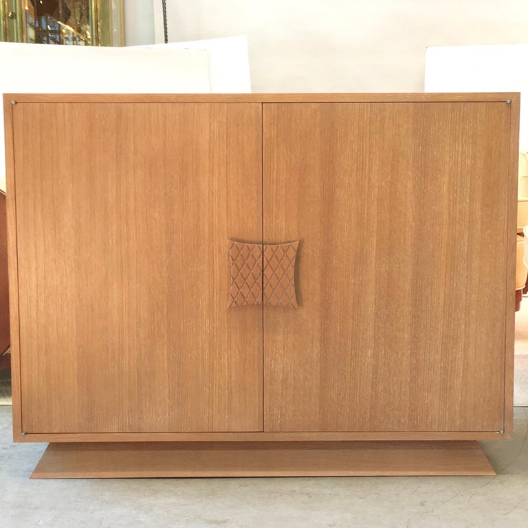 Presenting BG Galleries' exclusive re-edition of a custom design by Ernst Schwadron and executed in the workshop of Illi Kagan in 1949. Two door cabinet of harmonic proportions, constructed of white oak set on a trapezoidal plinth base and a single