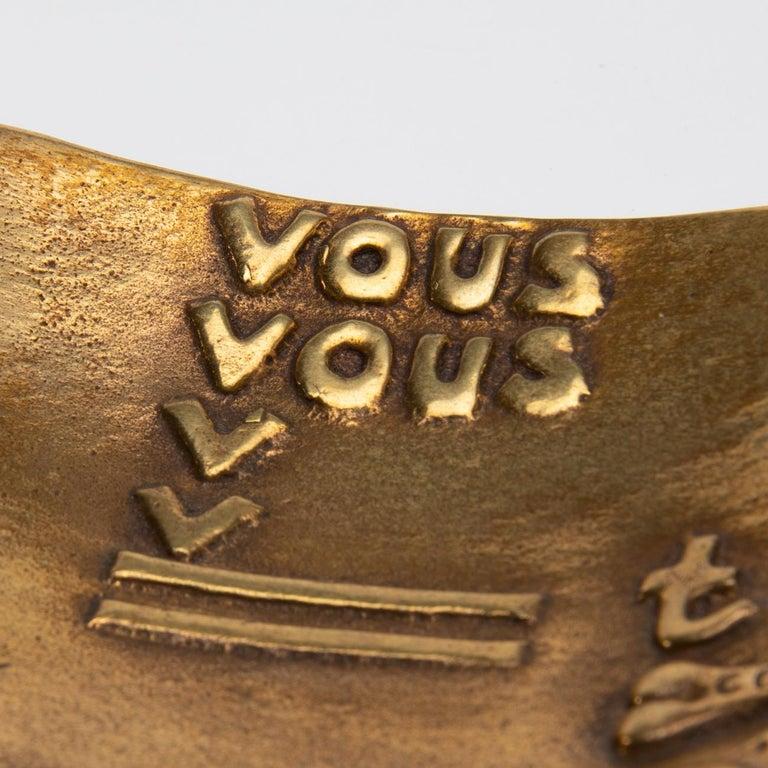 "In Greek mythology, Eros is the God of Love.  This trinket bowl presents a rebus saying ""Vous vous devez de traiter Eros comme un Dieu hâtez-vous"", which means ""Hurry, you have to treat Eros as a God"" in French.    VOUS VOUS (Vous vous)  Two V"