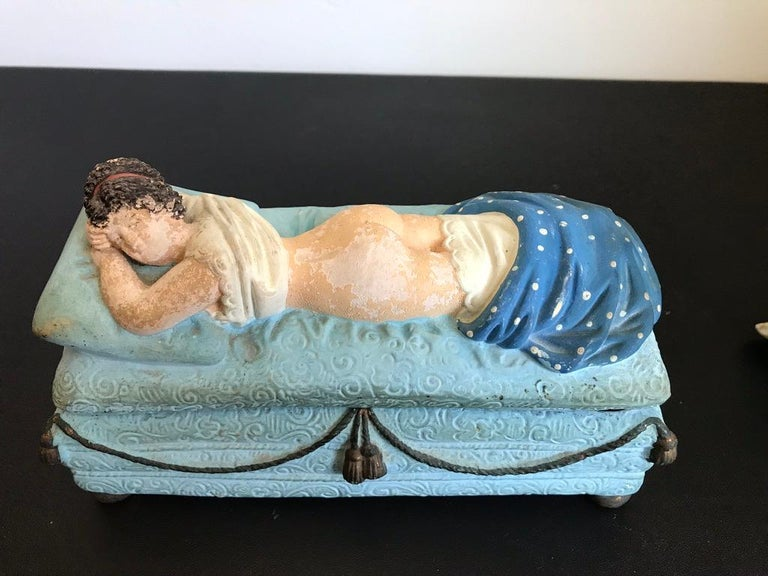A fun and amusing ceramic box with an erotic reveal. Remove her blanket and she is naked underneath. She is laying on her pale blue day bed with gold tassels and feet, propped up on a pillow looking over at the viewer with a knowing glance. Only she