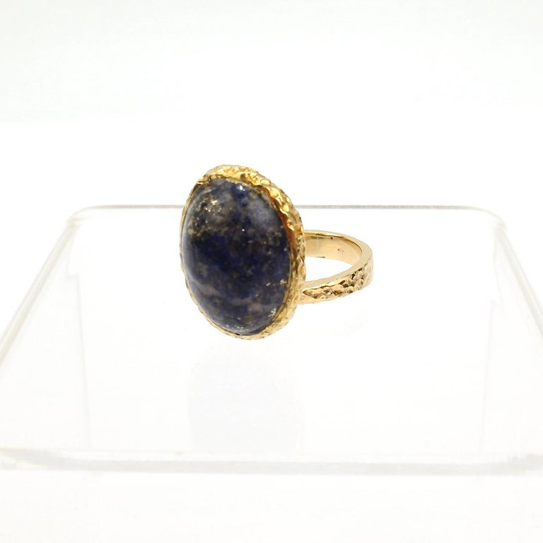 A very fine 18k gold and lapis cocktail ring by designer Erwin Pearl.  The asymmetrical ring features an oval lapis lazuli cabochon in an organic bezel setting.   Terrific modernist design!  Date: 20th Century  Overall Condition: It is in overall