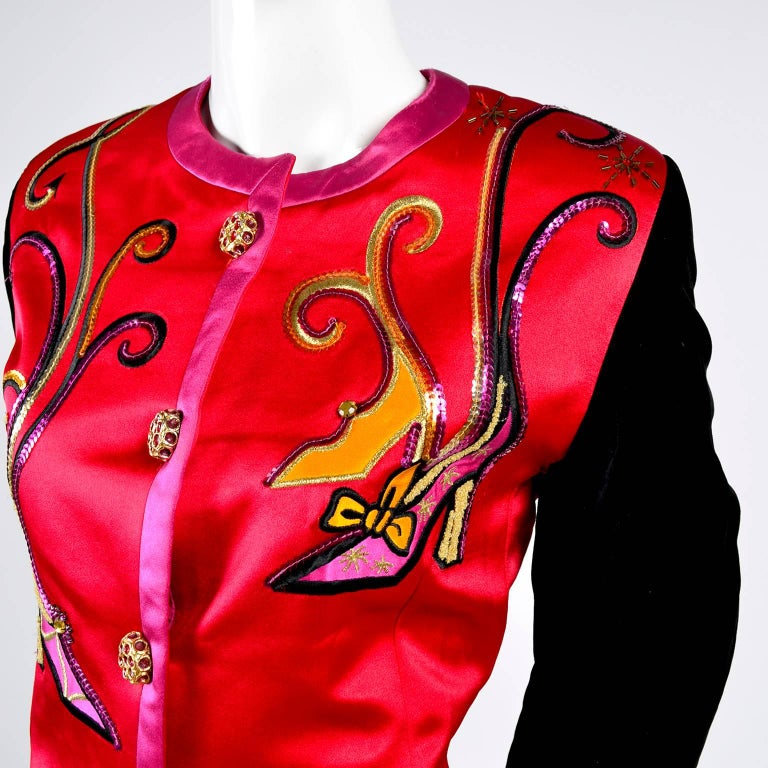 This 1980's vintage Escada jacket is in red satin with pink satin trim and has long black velvet sleeves.  The blazer has fabulous gold buttons with pink