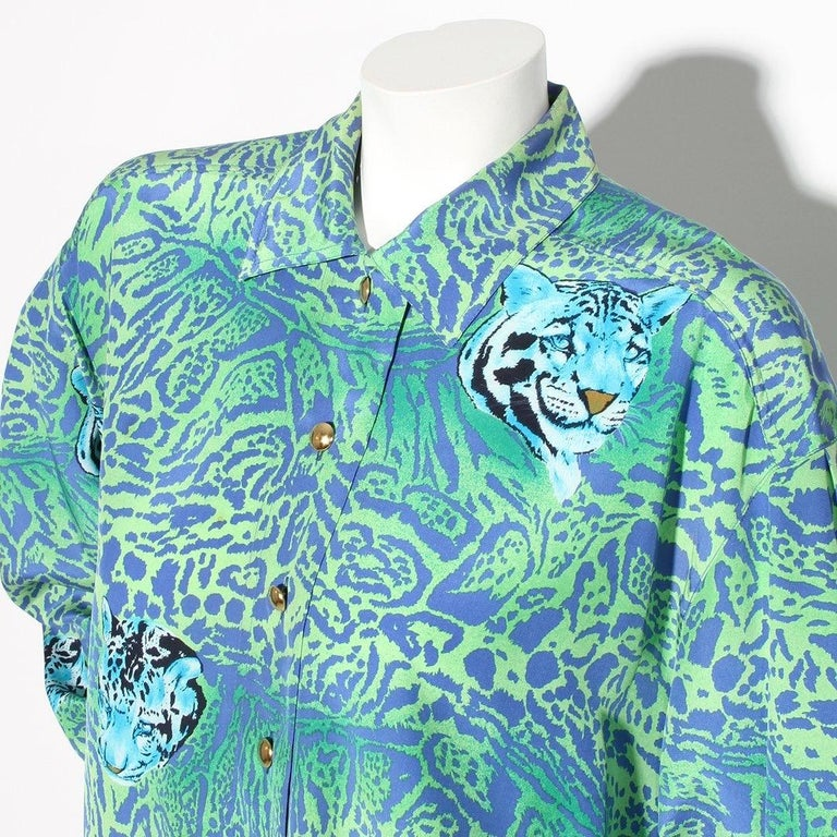 Cheetah print blouse by Escada Circa 1980's  Cheetah print with Cheetah heads throughout  Long-sleeve top Blue and green  Button-front closures Pointed collar Button cuff closures Gold-tone hardware  100% silk Made in Italy Condition: Excellent,
