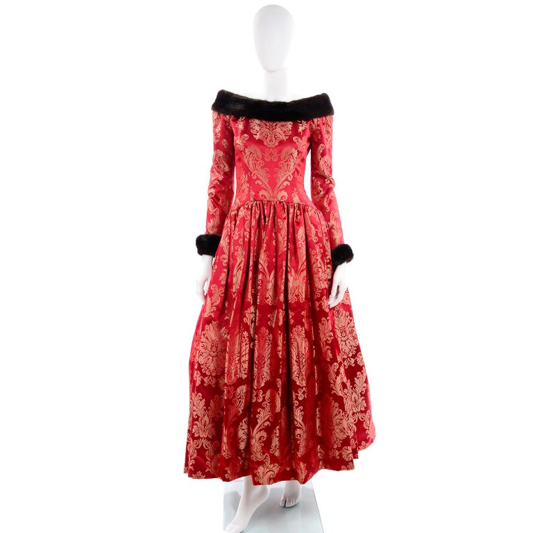 This sensational vintage ball gown from Escada Couture is in a luxe red jacquard and is trimmed in mink. The fur cuffs on the gorgeous evening dress are removable and the sleeves have zippers and button closures. There is a zipper down the center