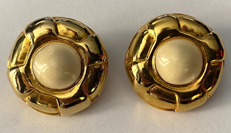 A very lovely pair of Escada button style clip earrings circa 1980. Each earring measures 1.19 inches in diameter and .38 of an inch deep, not including the clip back. The centers have a .5 inch diameter of ivory enamel. Each earring has an oval