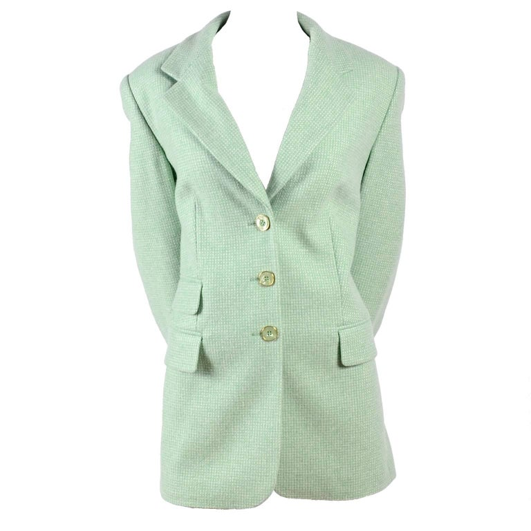 This vintage Escada blazer was designed by Margaretha Ley and is made of 100% cashmere and lined in Escada logo printed green rayon satin. The jacket has 3 Escada marked buttons on the front and 3 of the same green and gold logo buttons on each