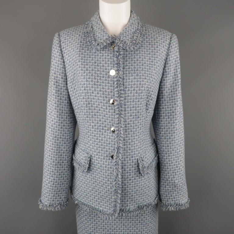 Vintage ESCADA suit comes in light blue cashmere tweed and includes a single breasted jacket with pointed collar, silver tone metal rhinestone buttons, flap pockets, and fringed trim with matching pencil skirt. Made in Italy.   Excellent Pre-Owned