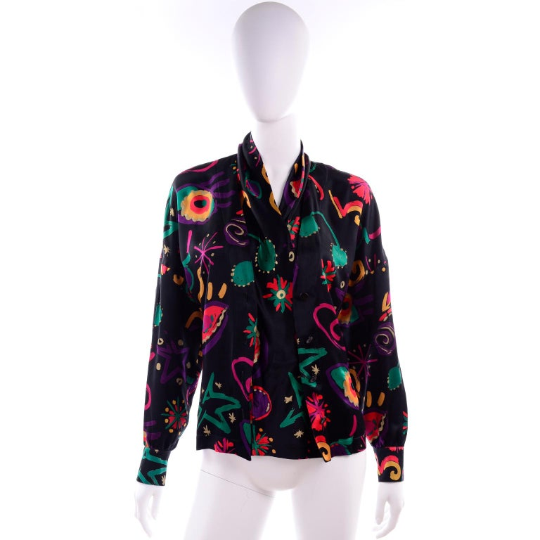 We love Escada blouses and this one is really incredible.  This was designed by Margaretha Ley in the 1980's. The blouse is in an abstract print silk and has black buttons down the front.  This top is in excellent condition and is labeled a size 38.
