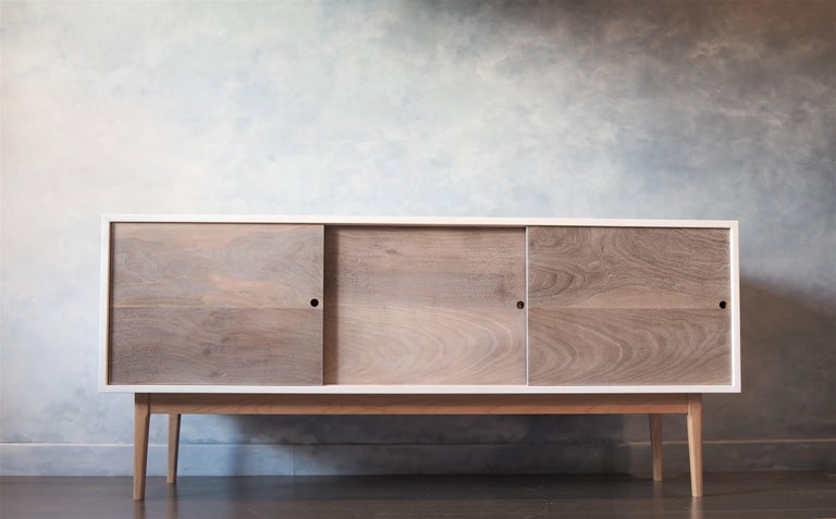 This fresh spring like side board is made with Oregon claro walnut sliding doors. The doors have been hand rubbed with pigment then thoroughly buffed back to leave an immaculate finish.   Copper slides are inset to give a subtle tone that highlights