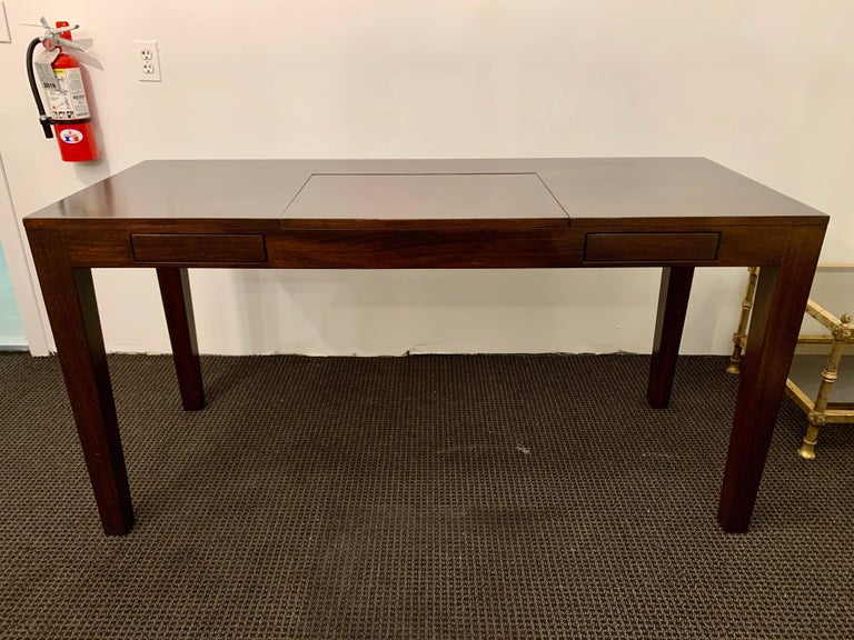 This Parsons style, simple and stylish desk has an added feature of a flip top vanity area with storage. Perfect for storing a laptop computer! Two push drawers to the left and right of vanity space in center.