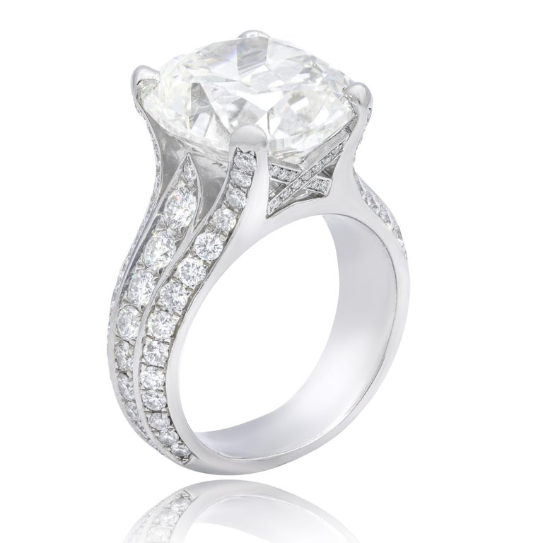Cushion cut Diamond Engagement Ring showcases a magnificent 10.73-carat, GIA-certified (GIA 16394978) cushion cut diamond (K color; VS2 clarity) in the center and 2.50 ctw of dazzling round diamonds on the sides.