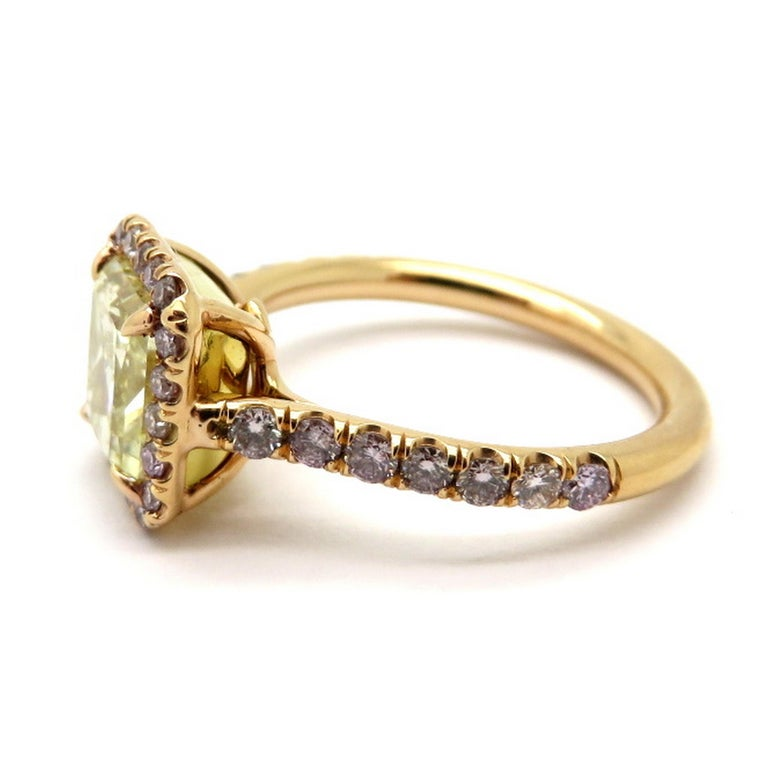 Estate 18K rose gold pink and yellow radiant cut diamond halo engagement ring. Showcasing one radiant cut fancy yellow diamond, four prong set, weighing approximately 2.00 carats, having SI1 clarity grade. Accented with 34 round brilliant cut bead
