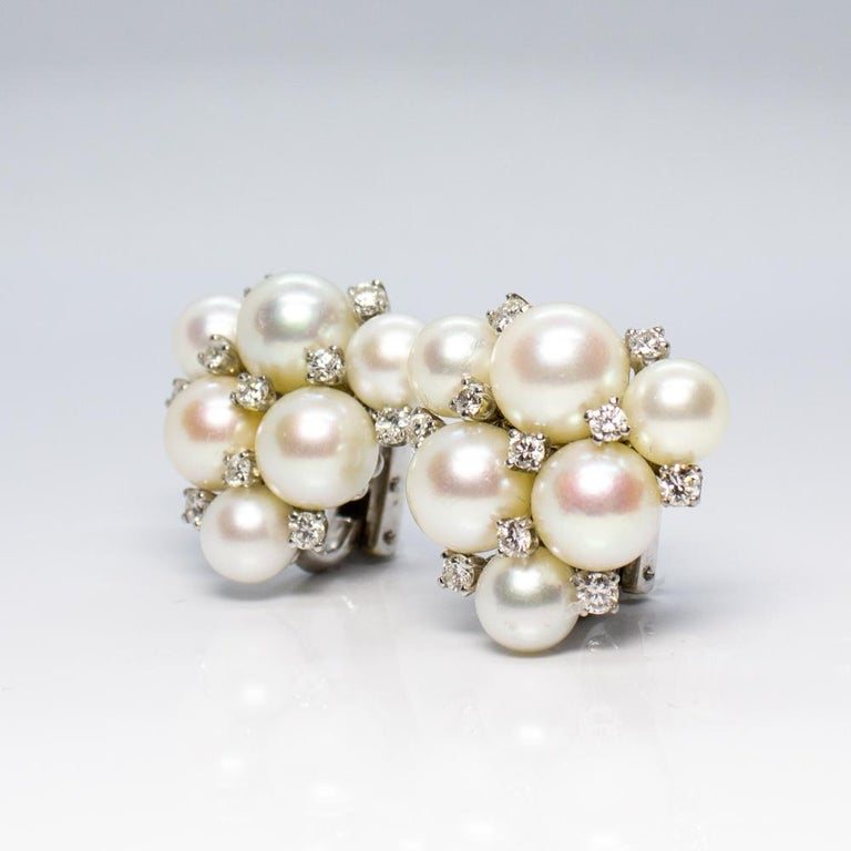 Estate 18K white gold Carvin French pearl and diamond cluster earrings.  Showcasing 20 round brilliant cut diamonds, crown set, weighing a total of 0.60 carats, having G–H color grade and SI1 clarity grade. Displaying six round white cultured pearls