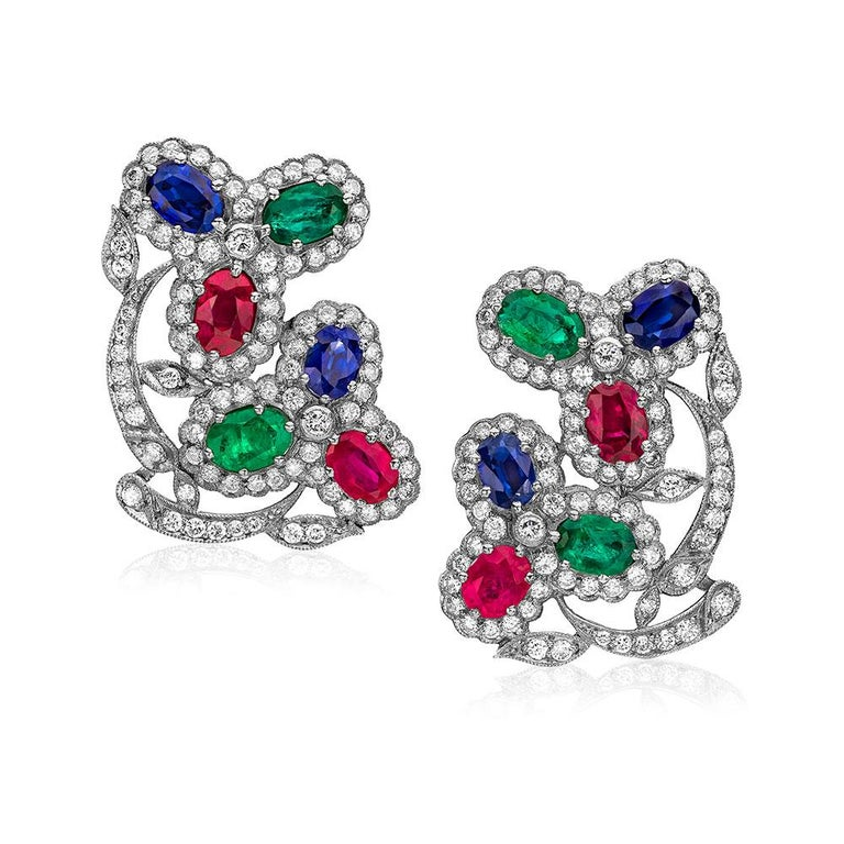 These stunning estate earrings are Designed in the art deco style, with colored gemstones surrounded by brilliant cut diamonds. Set in 18 karat white gold and 18 karat yellow gold, each earring design showcases two flowers composed of emeralds,