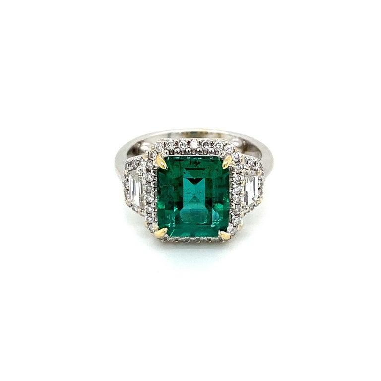 An exquisite ring set in 18k white gold, featuring a Rare vivid 3,34 ct. Emerald-cut Colombian Emerald, surrounded by 2 carats of Sparkling Round and Baguette shape diamonds, graded G color Vvs1 clarity.  The Emerald color is graded Intense bluish