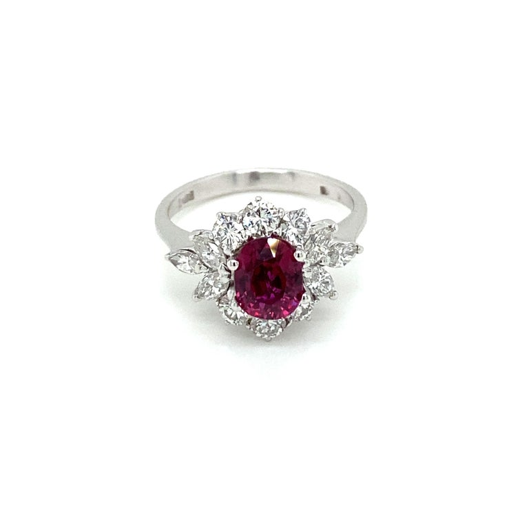 An exquisite cluster ring handcrafted in 18k white gold, featuring an amazing rare vivid 1.34 carat Unheated untreated Natural Burmese Ruby oval-shape, surrounded by 1.00 carats, twelve gems, of round brilliant and marquise cut diamonds, graded G