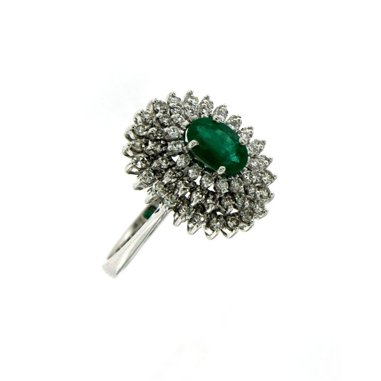 Beautiful cluster ring, hand-crafted in 18k white gold, centering a vivid oval-cut natural Colombian Emerald weighing 1.50 carat, surrounded by 1.50 carats of round brilliant cut diamonds G color VVS.  Origin Italy circa 1980  CONDITION: Pre-owned -