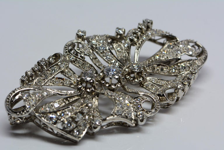 This estate brooch is handmade in platinum with accenting filigree and has a flowing ribbon motif throughout.  It contains one hundred and twenty-four round-brilliant cut diamonds, weighing approximately 2.98 carats in total.  The center diamond in