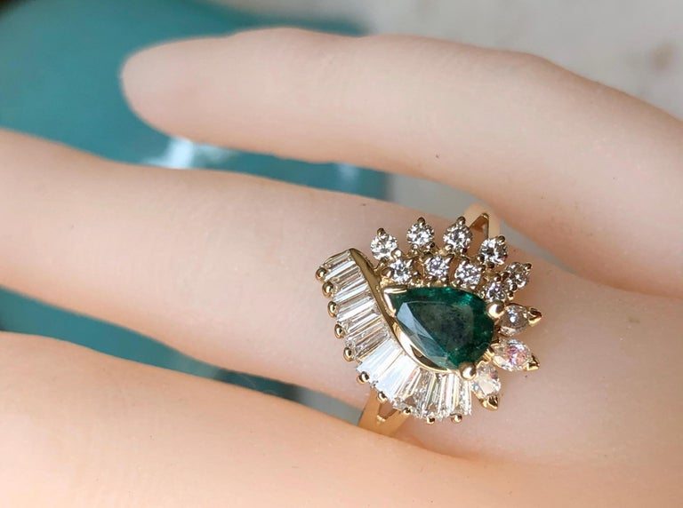 This beautiful estate cocktail ring features an emerald that weighs 0.90 carats, pear cut, dark green in color, SI in clarity. The emerald is framed by 21 diamonds in baguette, round, and marquise shapes. These diamonds weigh a total of 0.97 carat,