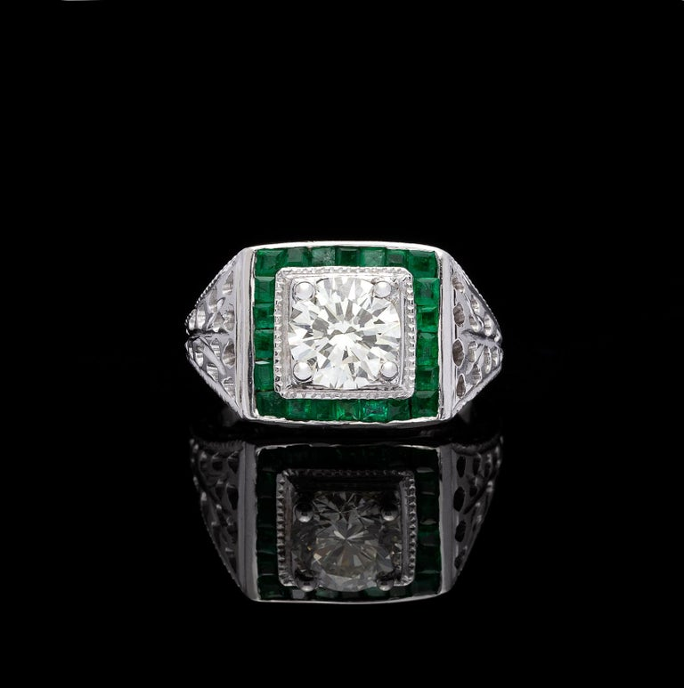 With vintage flair, this 18k white gold square halo ring is unique and wearable. Centering a 1.01 carat round brilliant-cut diamond, framed within a halo of 22 square-cut emeralds, with wide pierced shoulders which add a delicate, lacy look. The