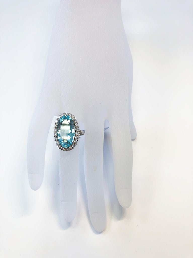 Stunning 10.80 carat greenish blue paraiba tourmaline oval with GIA certificate.  Surrounded by good quality, bright, white diamonds weighing 1.70 carats in a platinum size 6 mounting.  Good quality paraiba with a bright blue green crystal that is