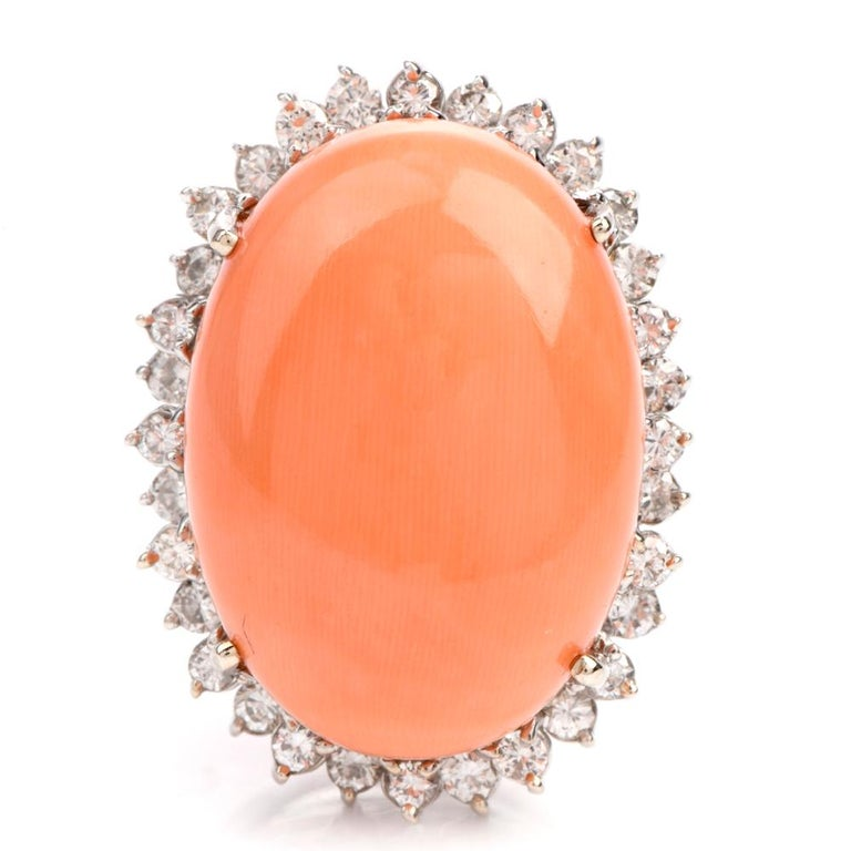 The beautiful cocktail ring features a very large soft pink oval shaped  cabachon cut natural Coral measuring appx. 18.99 x 26.1 x 11.15mm High.  Offering dimension to the outer rim of this ring are 32 diamonds  alternating on 2 eneven rows.