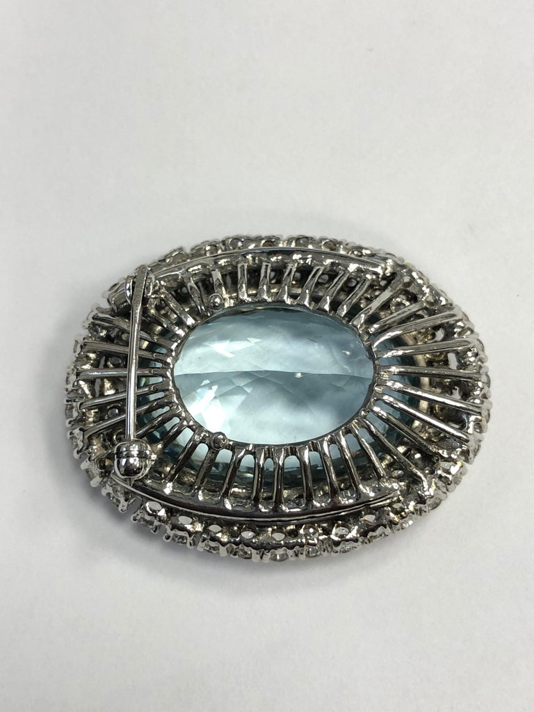The pin is stunning, a grand statement piece, centered on an approximately 30 carat fine Aquamarine surrounded in a multi-halo with approximately 6 carats of full cut diamonds G-H Color VS-SI Clarity.