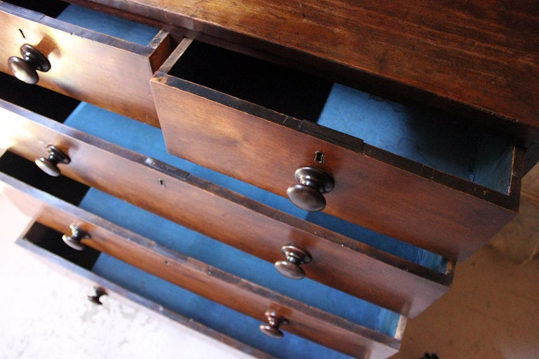 The mid-Victorian period estate made cherrywood carcass of fine overall color, having mahogany bandings to the drawers, the graduated drawers of two short and three long opening to reveal old blue paper linings, each having the original locks, knob