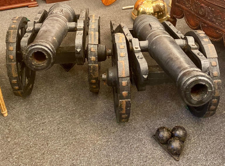 Estate 20th century pair of cast iron reproduction 19th century American cannons and caissons. Includes two sets of three matching cannonballs and their accompanying stands. Cannons are exclusively for decorative use. Wheels function and cannon can