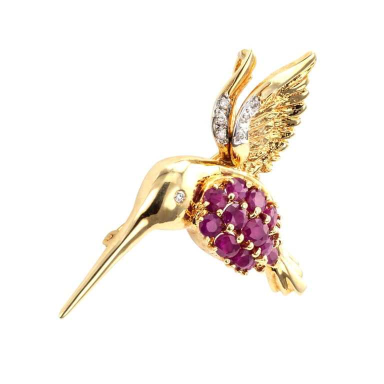 Estate ruby diamond and gold hummingbird brooch pendant circa 1980.  DETAILS: Estate ruby diamond and gold hummingbird brooch pendant. GEMSTONES: thirteen round rubies. DIAMONDS: seven round brilliant-cut diamonds totaling approximately 0.04