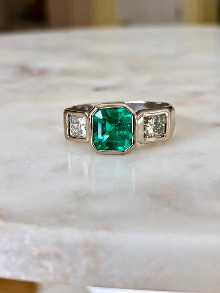 Natural Colombian emerald, diamond and 18K white gold ring, centering 1 bezel-set, emerald-cut, square emerald with bezel-set princess-cut  diamonds. Emerald is beautiful displaying excellent color and clarity.  100% Natural Colombian Emerald AAA