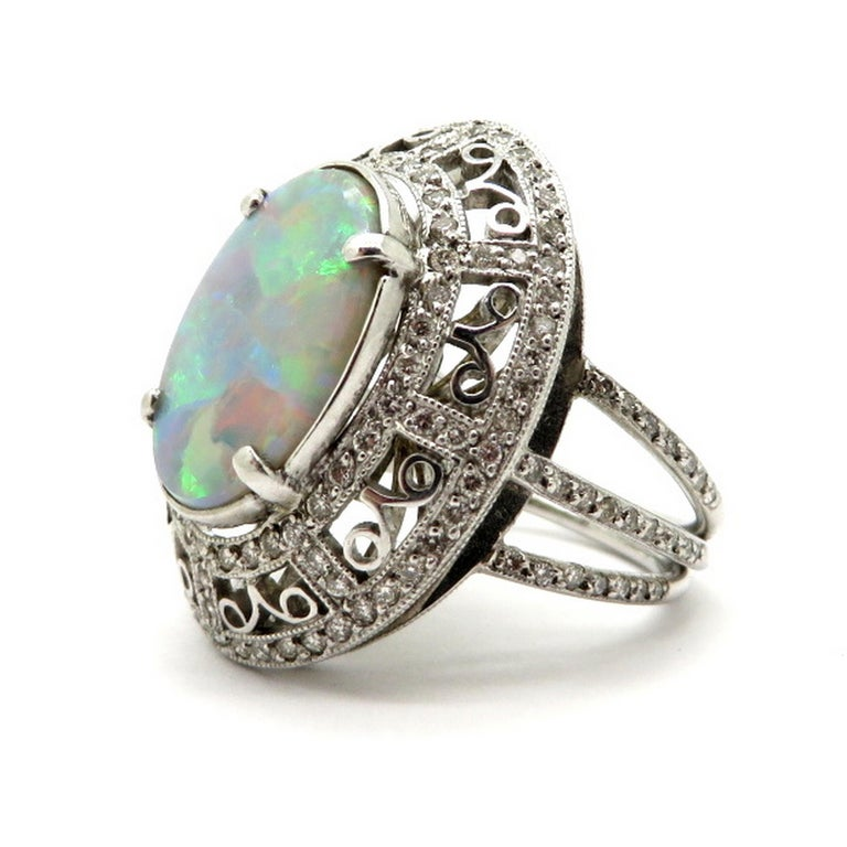 Estate Vintage platinum 2.03 black Opal diamond halo ring. Showcasing one oval black Opal, measuring 14.58 x 10.20 mm, weighing approximately 2.03 carats. Displaying 164 round brilliant cut bead set diamonds weighing 0.75 carats, having H – I color