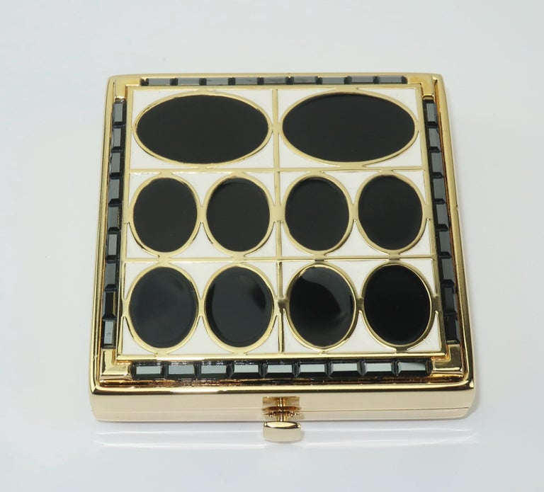A collectible powder compact from Estee Lauder with an Art Deco motif in black and white enamel accented with black (almost gunmetal) rhinestones in a jewelry quality gold tone metal.  The push button closure opens to reveal a mirror and a