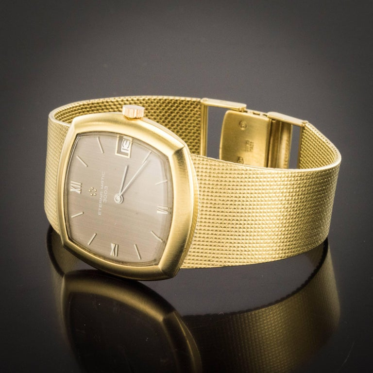 Watch in 18 karats yellow gold, owl and weevil hallmark. Square shape, this vintage gold watch is ultra-flat. The bracelet is a braided mesh ultra flat and flexible. The clasp is on a scale. The dial is glossy brown. Height of the dial: 3.3 cm,