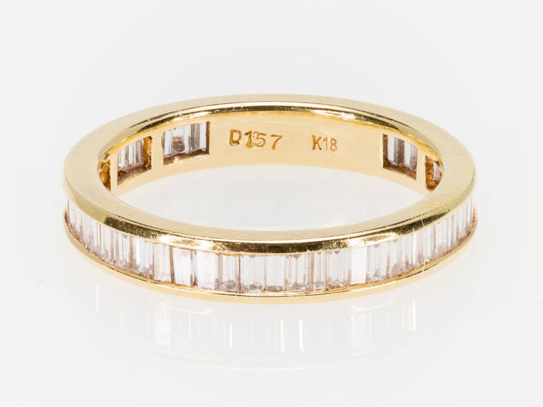 An American Eternity baguette cut Diamond band ring circa 1980 in 18K yellow gold, size 6 ¾. This Eternity band wedding ring features baguette-cut Diamonds of an approximate total weight of 1.57 carats. The diamonds grade is IJ color and VS-SI