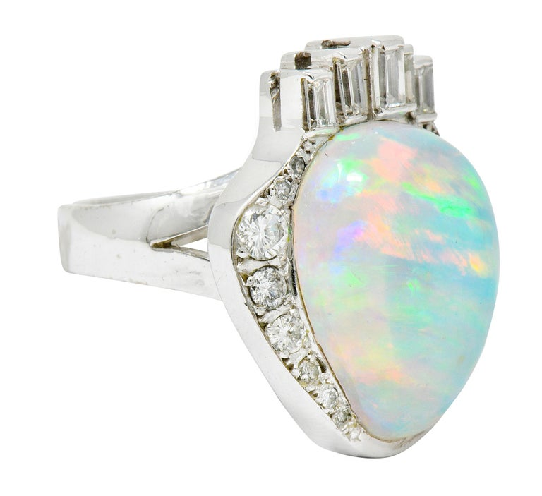 Centering a pear shaped jelly opal cabochon featuring spectral play-of-color  With abstract baguette and round brilliant cut diamond surround weighing approximately 0.75 carats total; G to J color with VS to I clarity  Overall ring is designed as a