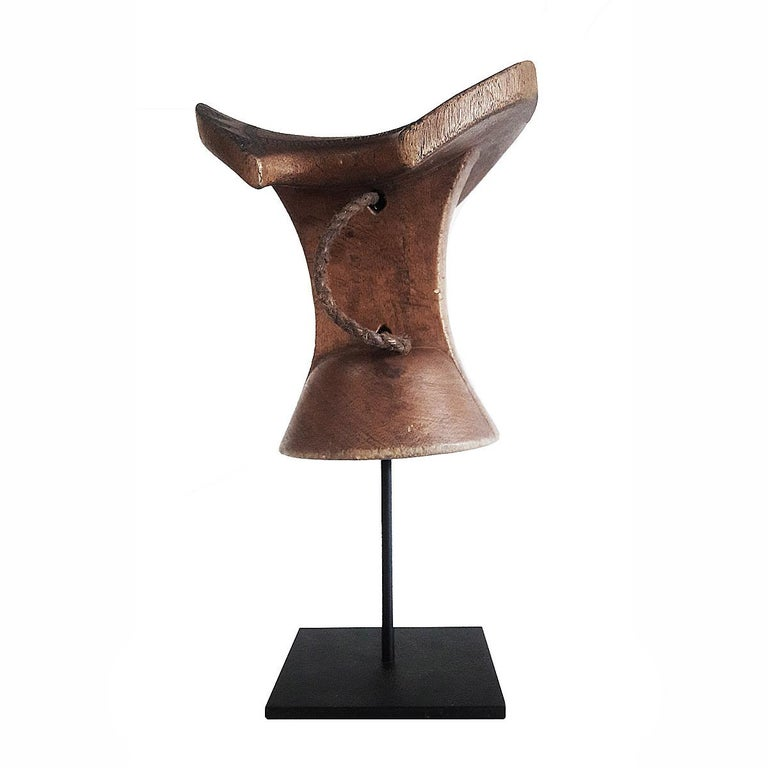 A headrest or stool, hand carved out of a single piece of teak wood, and decorated with traditional carvings, with a braided leather handle. Ethiopia, late 20th century. Mounted on a black metal stand.