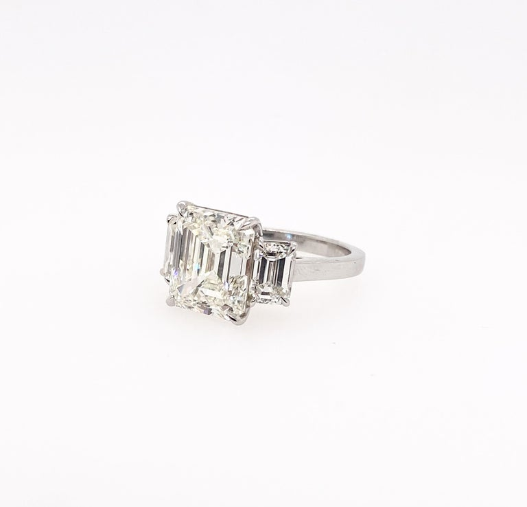 This three-stone ring is fully set with the certified Emerald cut diamonds. The 5.82carat with IGI Certificate emerald cut diamond in the center is perfectly accentuated with two beautifully certified emerald cut diamonds mounted on the side