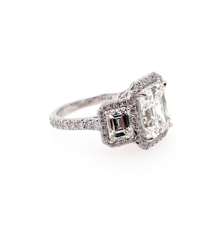 Beautiful GIA Certified 6.13carat Asscher cut diamond mounted in Platinum ring as a center stone. It is set with two GIA certified emerald cut diamonds, 0.90 carat respectively. In additional, the round shape side diamonds 68pc framed that three big