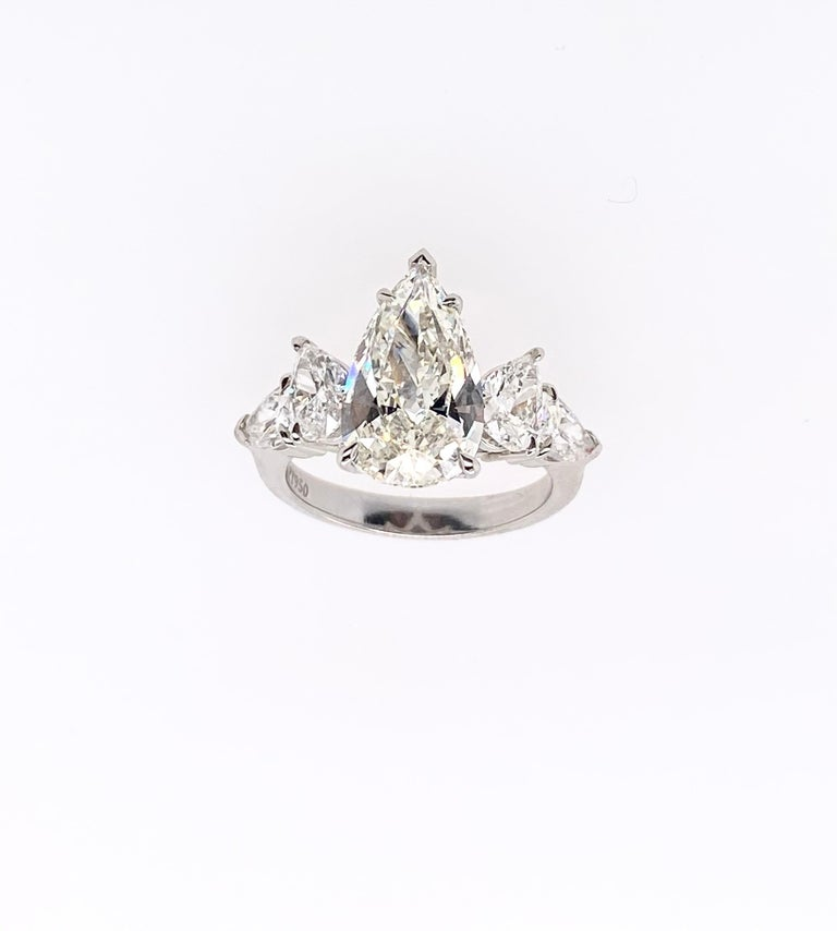 GIA Certified 3.23 carat pear shape diamond is perfectly accentuated with another two beautifully pear shape diamonds per side (as total four pear shape diamonds for both sides) mounted respectively in platinum ring. This stylish four-stone ring
