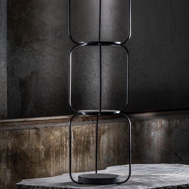 Part of the Tarsie Geometriche collection, this bookcase is a sculptural masterpiece. Varnished with an opaque black powder, the linear iron structure creates a striking silhouette with four black tops made of volcanic stone with a honed finish,
