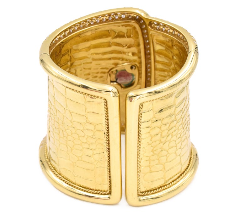 Etoile diamond cuff watch made in 18k yellow gold. The front half of the cuff around the edges, face of the watch, halo and leaf designs around the watch are pave set with round brilliant cut diamonds. Accented with larger marquise and pear shape