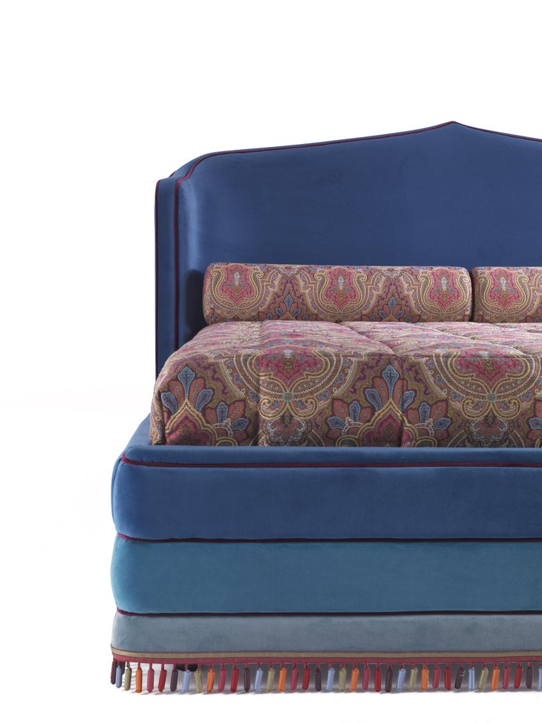 A fairy-tale bed inspired by a 'thousand-and-one-nights' imagery. The arabesque shape of the headboard, the intense turquoise color with purple piping and the precious and the multicolor passementerie contribute to create a magical and sophisticated