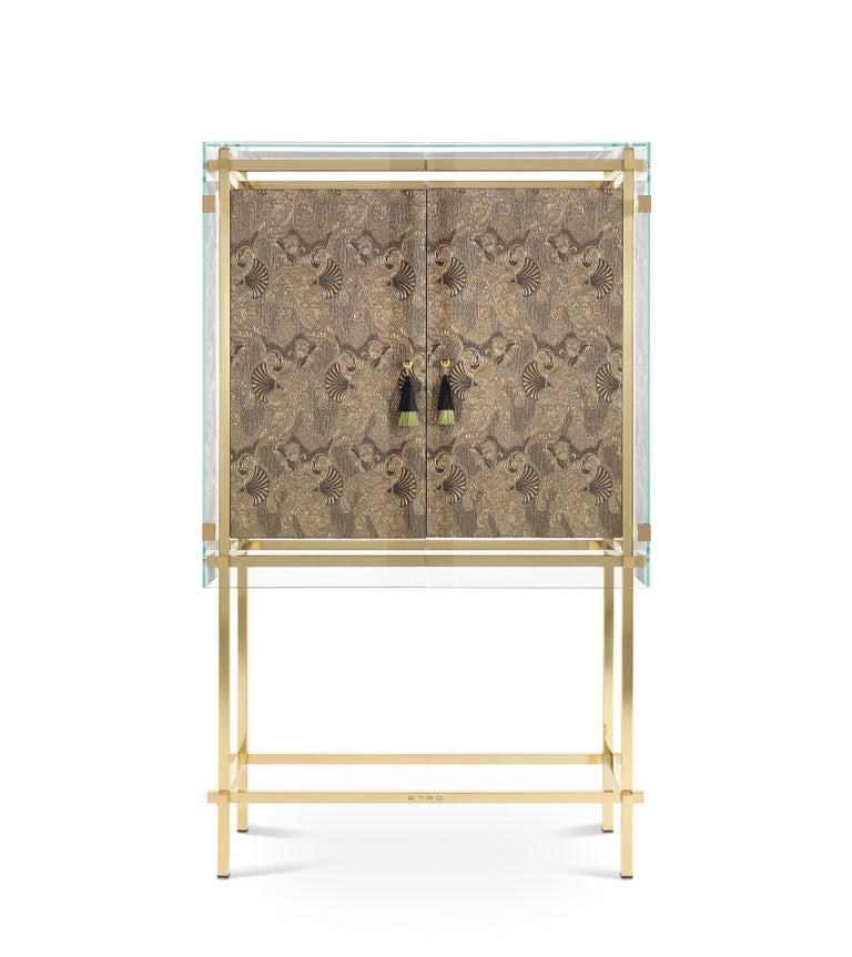 An impactful cabinet featuring a precious upholstery in fabric from the Etro Home Interiors collection with oriental inspired decorative motives and outer extraclear tempered glass. A mystic and transcendent element with an ethereal and luminous