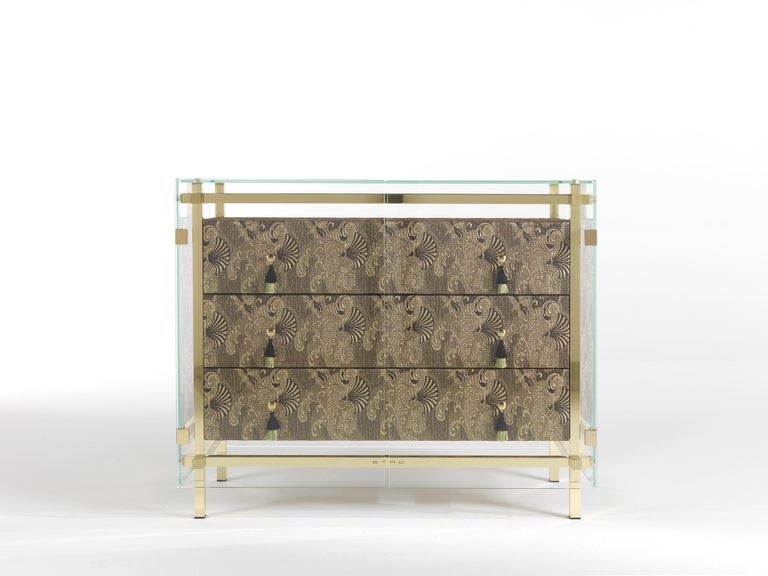 An impactful chest of drawers featuring a precious upholstery in fabric from the Etro Home Interiors collection with oriental inspired decorative motives and outer extraclear tempered glass. A mystic and transcendent element with an ethereal and