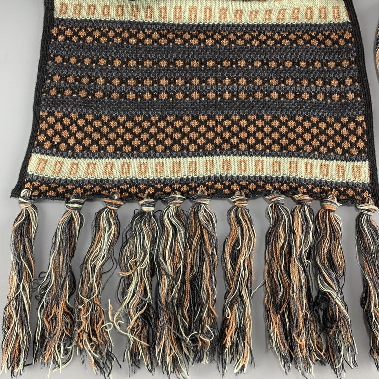 ETRO scarf comes in a wool blend knit with subtle sparkle throughout with black piping, navy and copper pattern, and fringe ends. Made in Italy.  Excellent Pre-Owned Condition.  118-130 x 14 in.