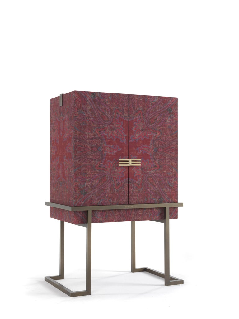 This evocative cabinet recalls the shape of an ancient chest, like those which were sorted in Kolkata, one of the primary commercial centres in India. Embellished by a patinated bronze base, the cabinet is covered with antiqued printed fabric with