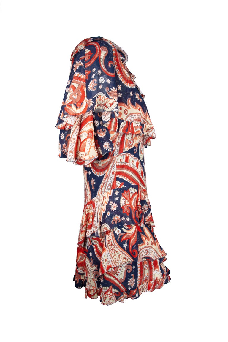 This Fall 2018 Runway Etro dress features a red and blue paisley print, silk tiered ruffles, side zipper closure, and a ruffled cape. Brand new with tags. Made in Italy.  Size: 40 (IT)  Material: Silk 100%  Colors: Red, Navy Blue, Beige